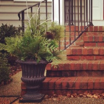 Urns with natural greenery flank the front porch steps